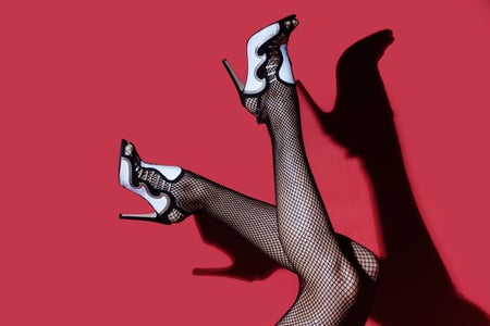 Black and white high heeled feet with silhouette in the background