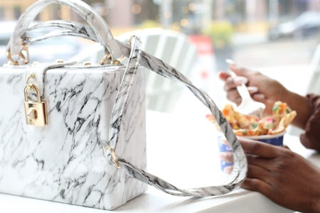 white purse with person eating dessert in the background