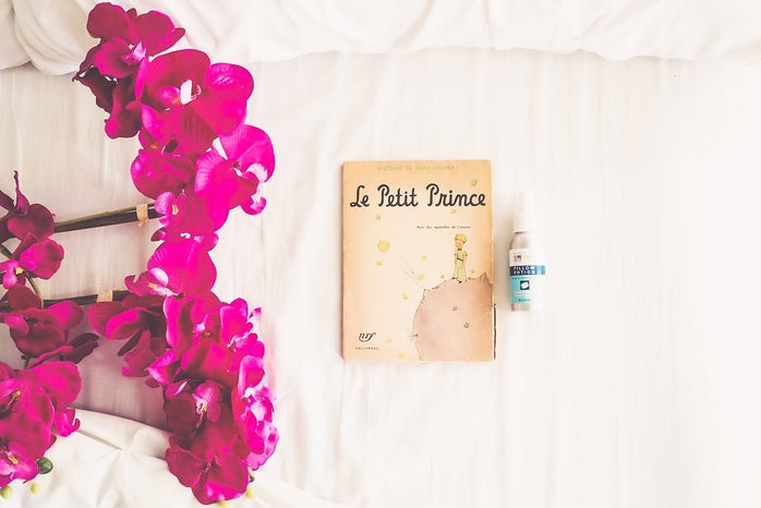 Book Le Petit Prince with pink flowers and essential oils on a white background