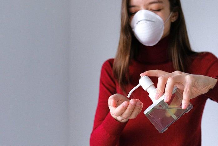 woman wearing mask using hand sanitizer