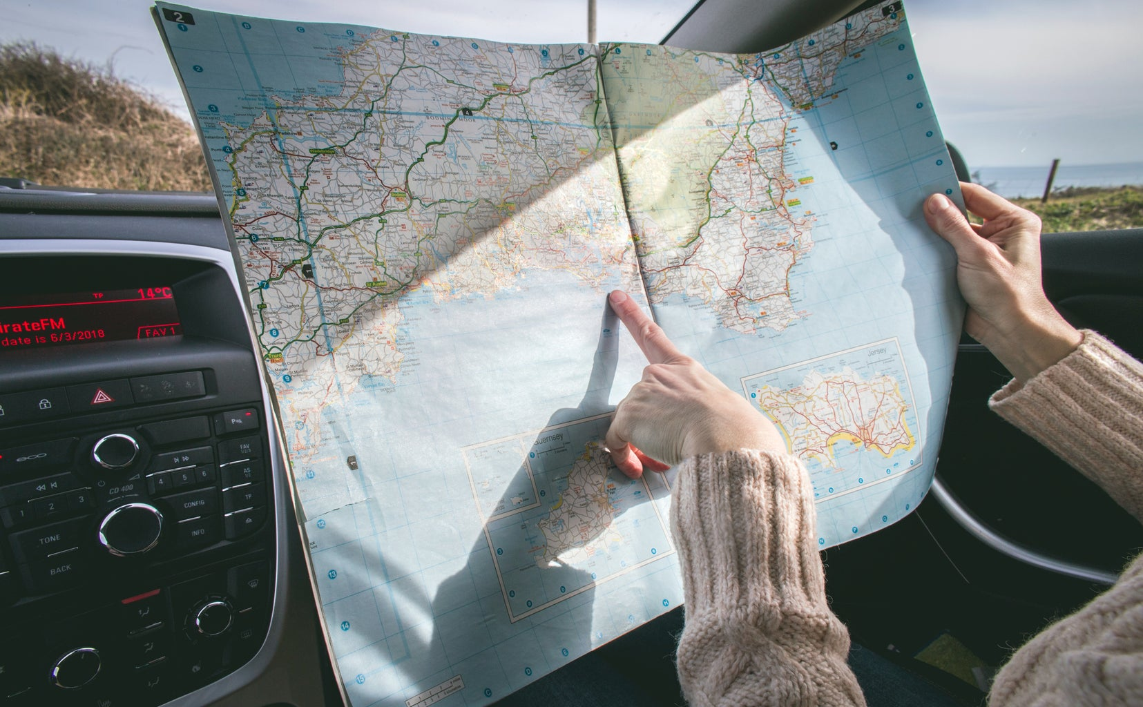 Person pointing at a fold-up map in a car.