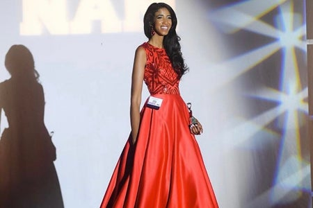 Girl is walking on stage smiling in a red gown with a trophy