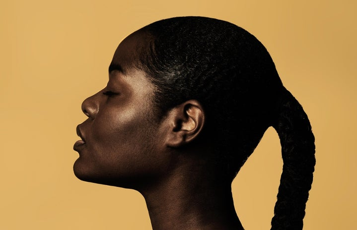 Woman highlighted by light on a yellow background