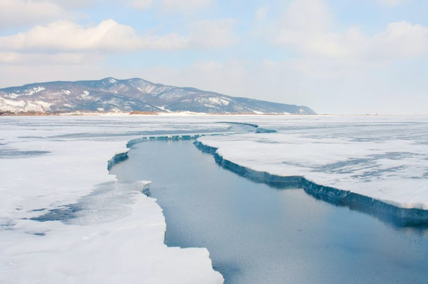 snow covered mountain near body of water during daytime at lake baikal in siberia, russia