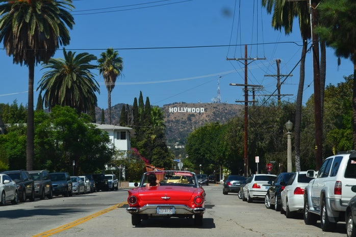 driving in red convertible with Hollywood sign in the distance
