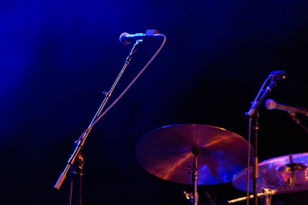 dark purple hues with microphone and drumset on the lower right