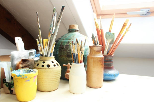 paintbrushes in pots on a table