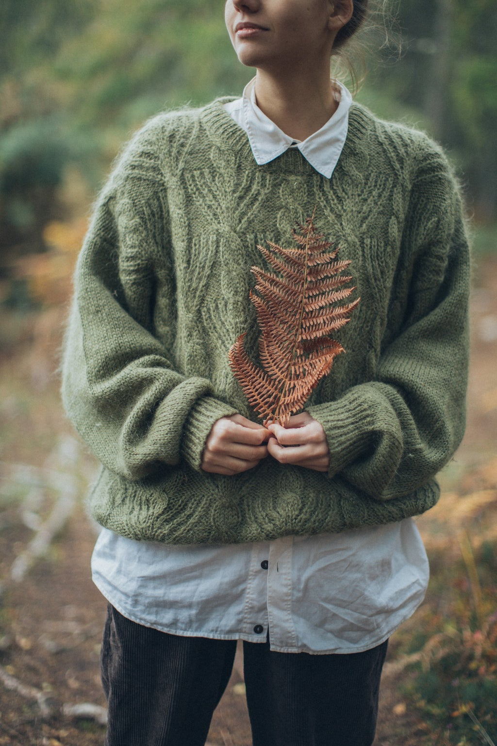 woman in sweater holding leaf