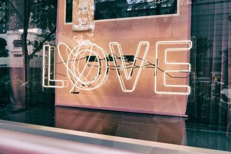 """the word """"LOVE"""" in a sign, lit up and in a window"""