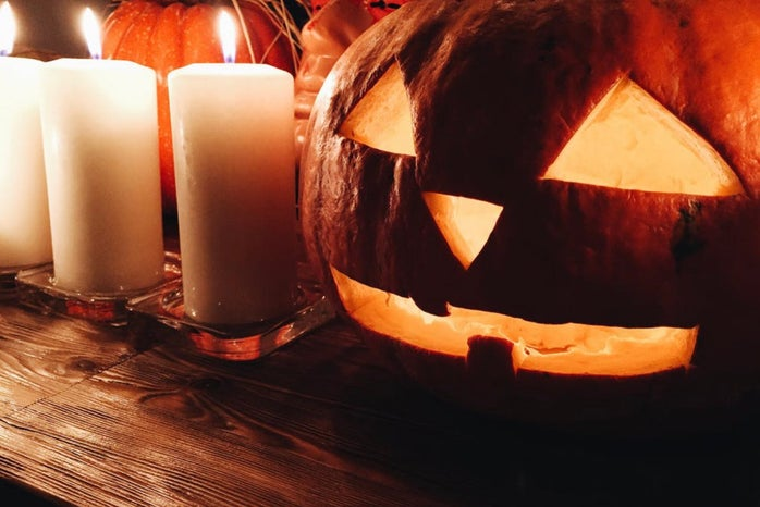 Carved pumpkin on table with candles