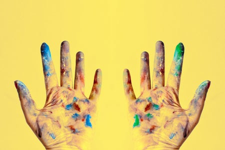 paint-splattered gloves against yellow background
