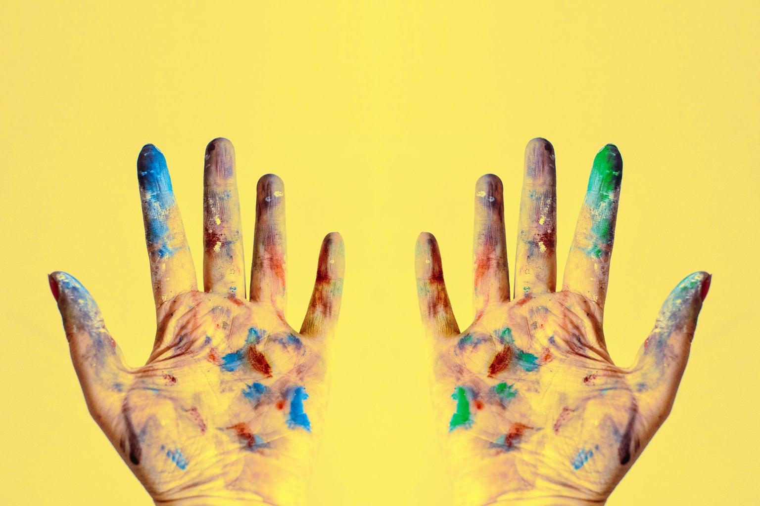 paint-splattered gloves against yellow background