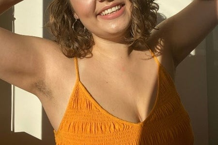 woman in a yellow shirt with her arms raised above her head