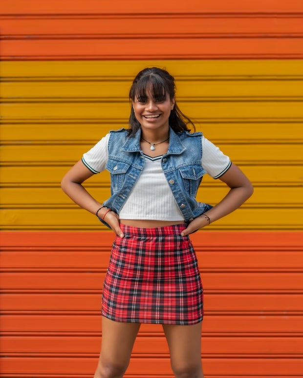 Woman wearing a plaid skirt and a white shirt