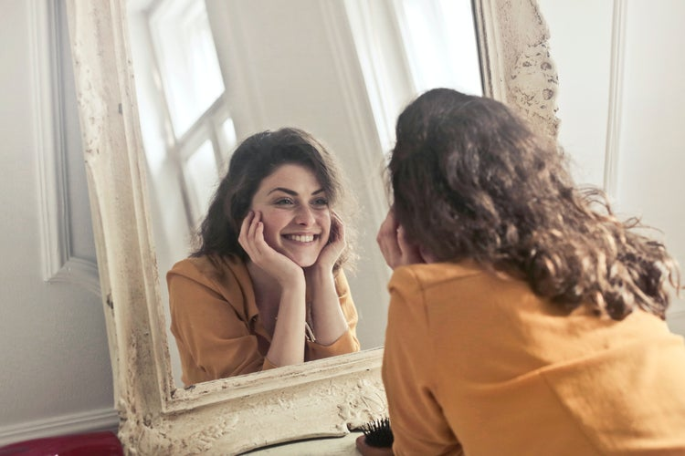 woman smiling at reflection in mirror
