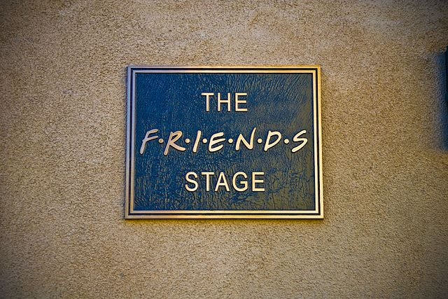 """plaque on a brick wall saying \""""The friends stage\"""""""