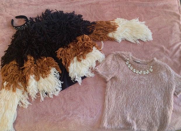 A fringe jacket and fuzzy top are displayed against a dusty rose background