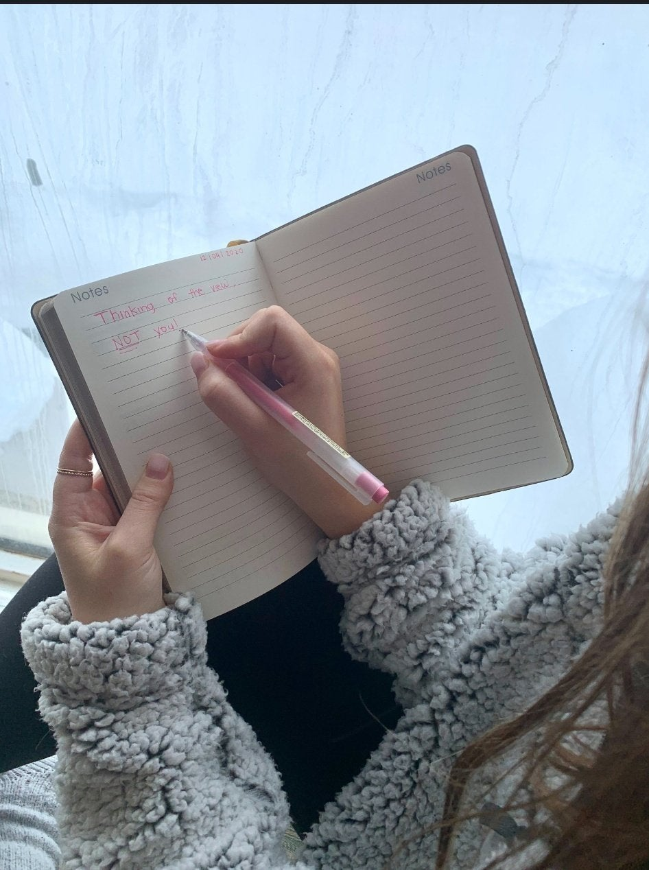 Girl writing in notebook with a pink pen ; pictured are Rachel Alter, Sasha Folgoas and Daphna Roytblat