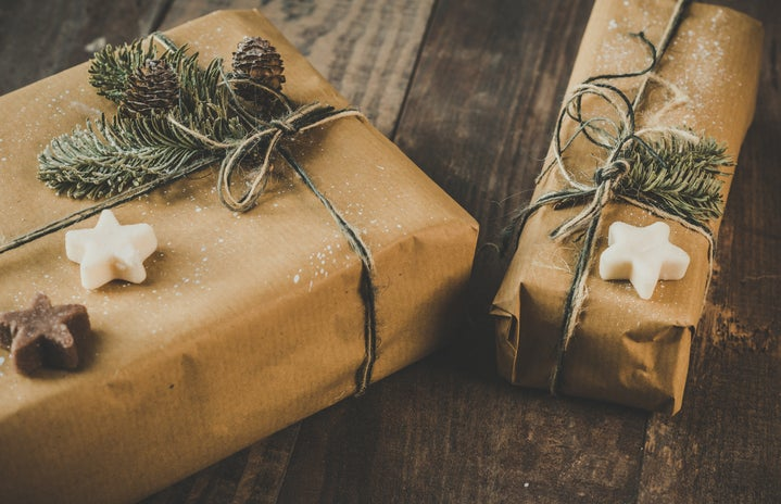 two gifts are wrapped in brown paper and covered with green and star-shaped soaps.
