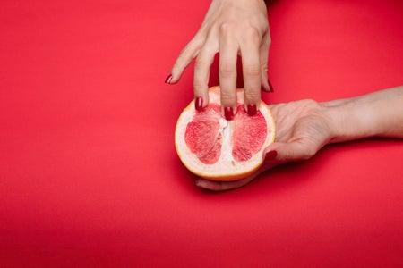 Hand touching grapefruit