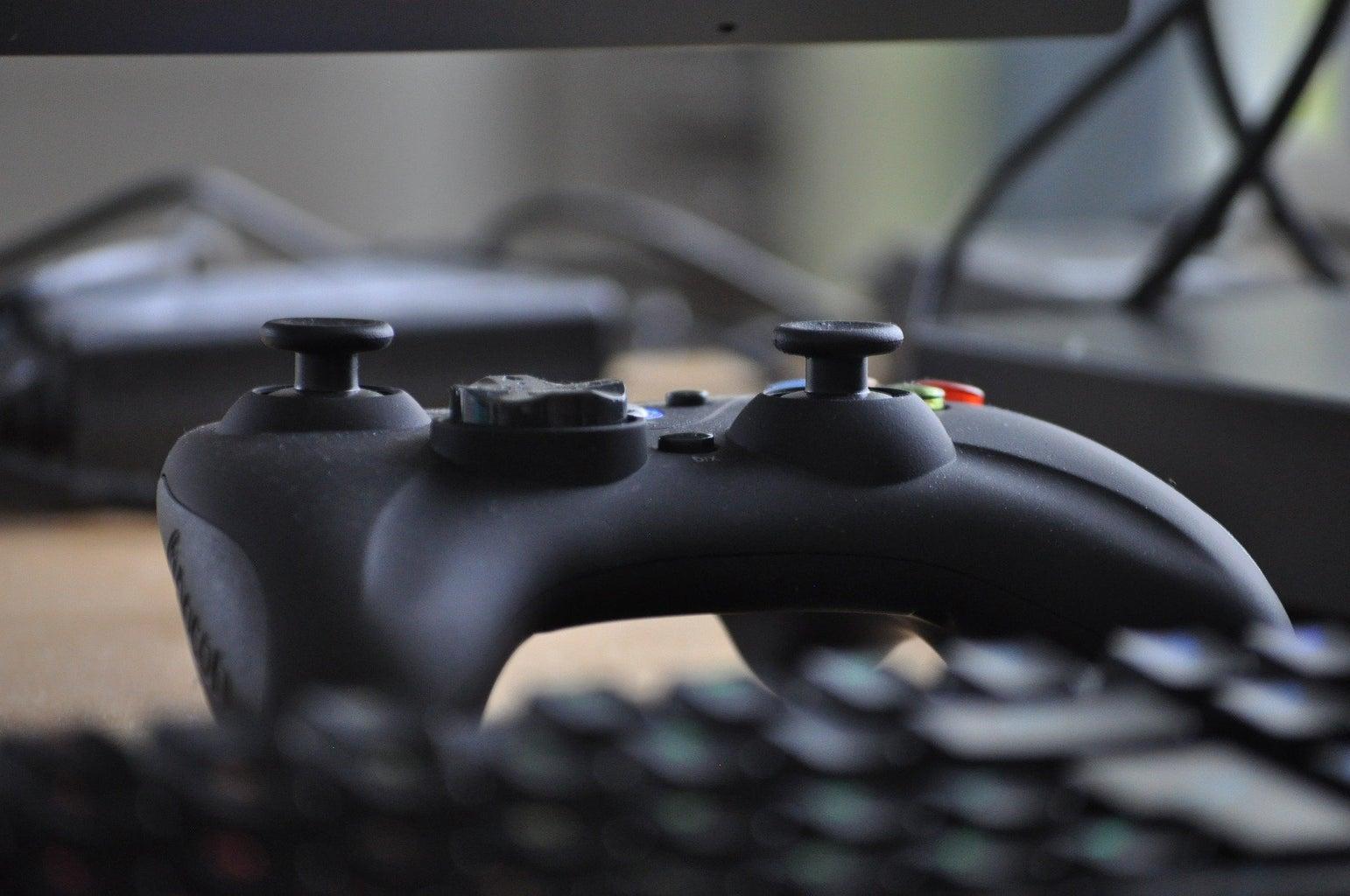 game controller sitting near a keyboard