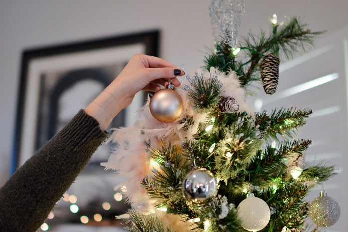 Hand putting ornament on tree