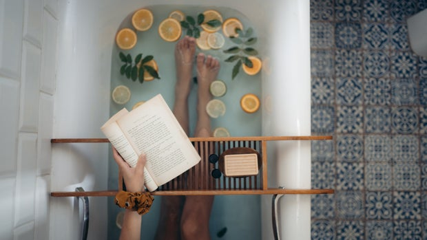 Person in a bathtub with lemons and herbs reading