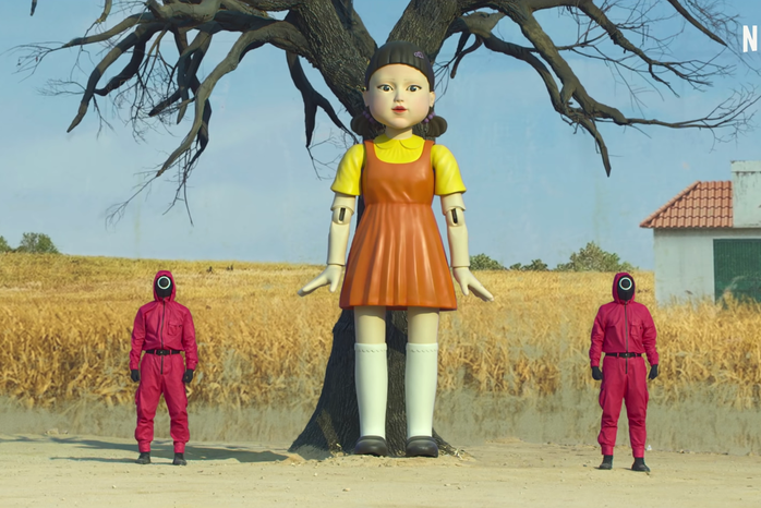 screenshot of a mechanical doll and two workers dressed in red from the Squid Game Official Trailer on YouTube by Netflix