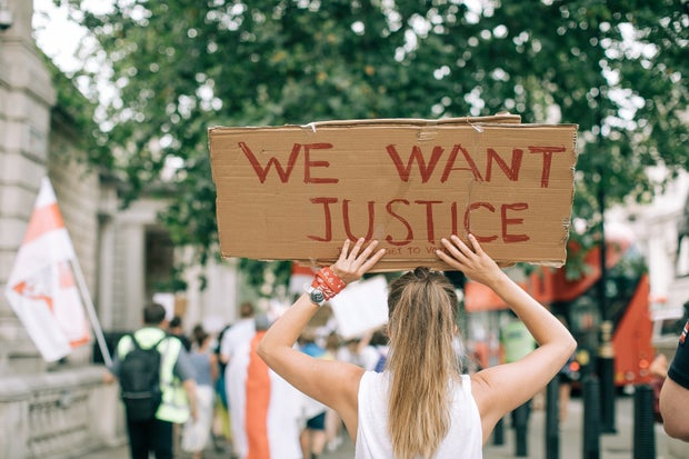 We want justice cardboard and girl with blonde hair