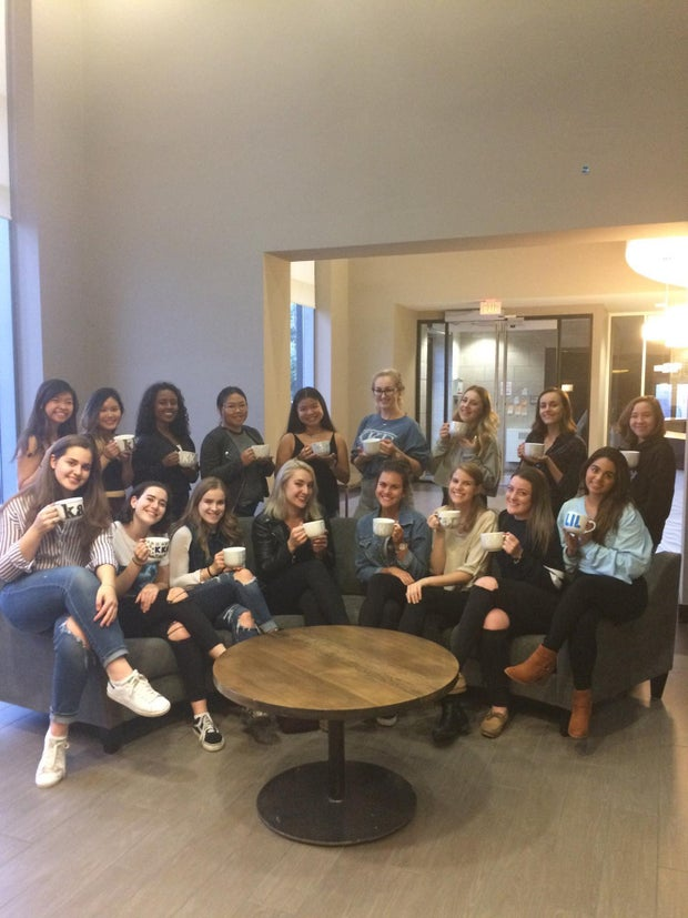 group of sorority sisters holding decorated mugs