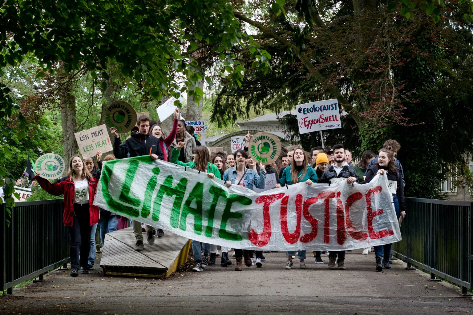 """people marching with sign that says """"climate justice"""""""