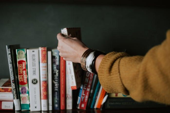person picking a white book off a bookshelf