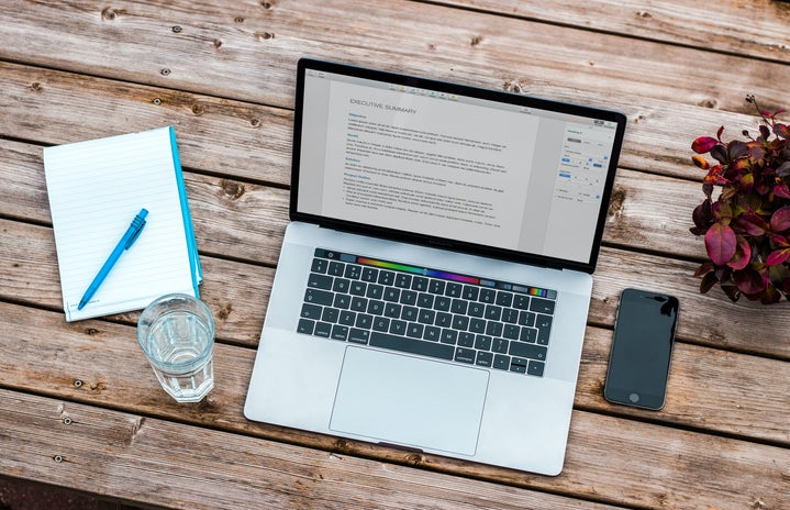 silver MacBook beside space gray iPhone 6 and clear drinking glass on brown wooden top