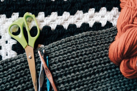 Crochet tools and yarn laid on top of blankets.