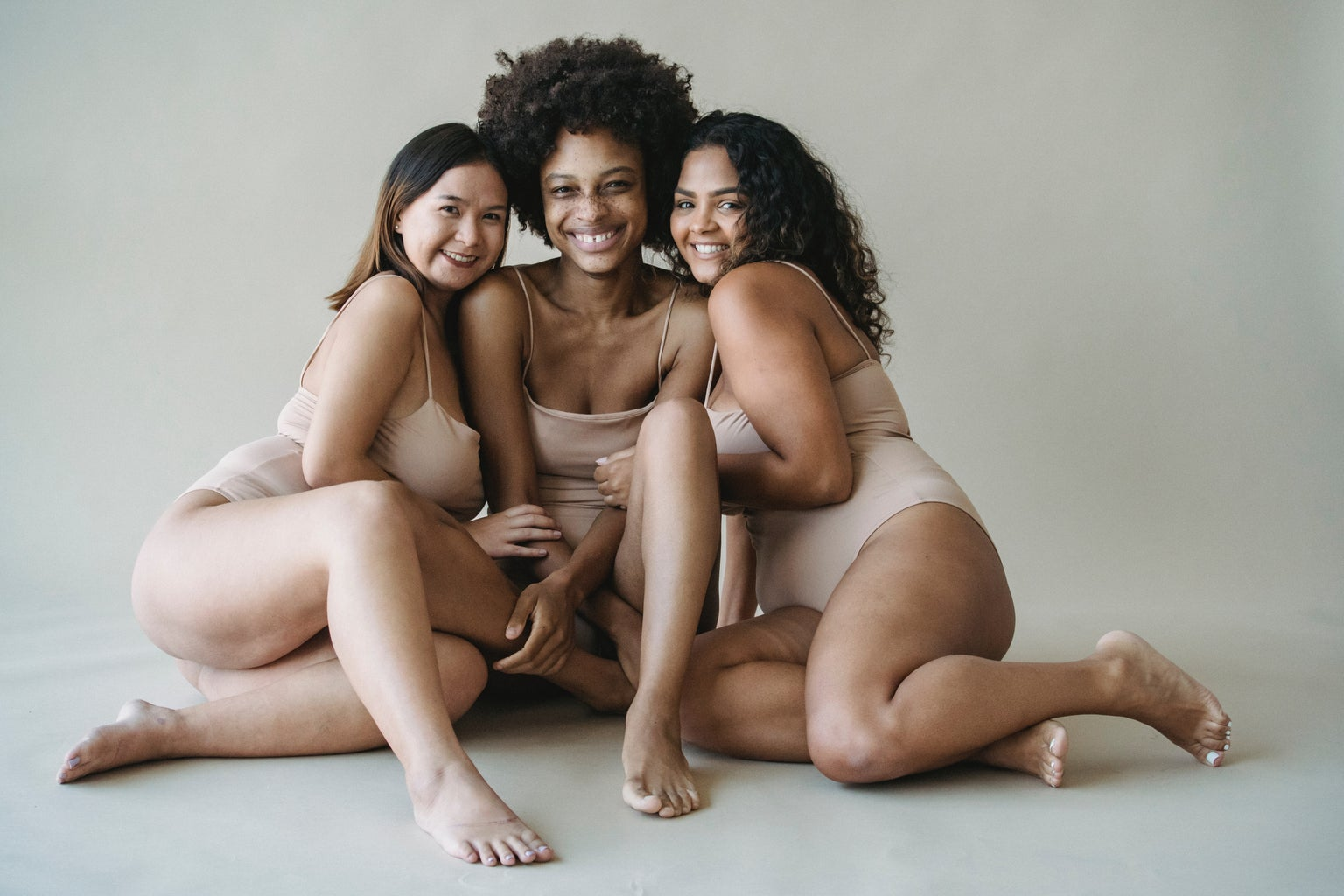 three women in brown tank tops and shorts against a white backdrop