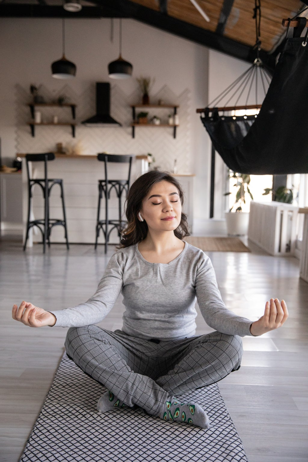Woman in all gray meditating on a yoga mat on the floor in her apartment.