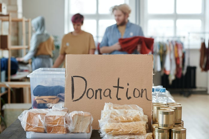 """a cardboard with """"donation"""" written in it, between some donation items"""