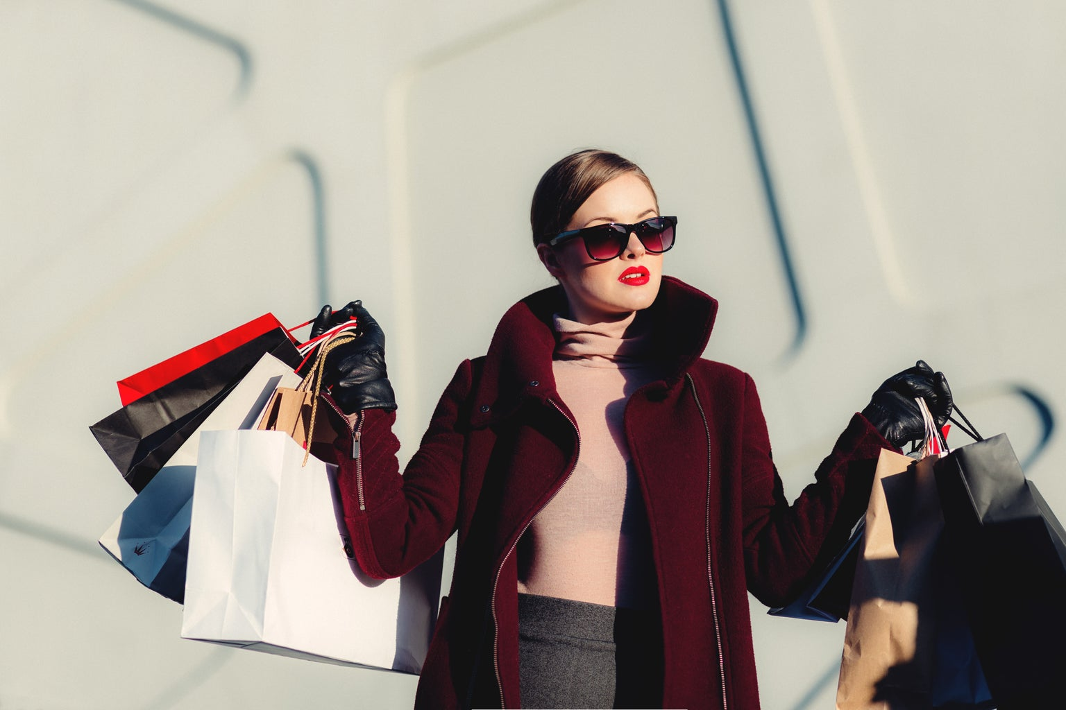 Woman with magenta coat and sunglasses holding up shopping bags