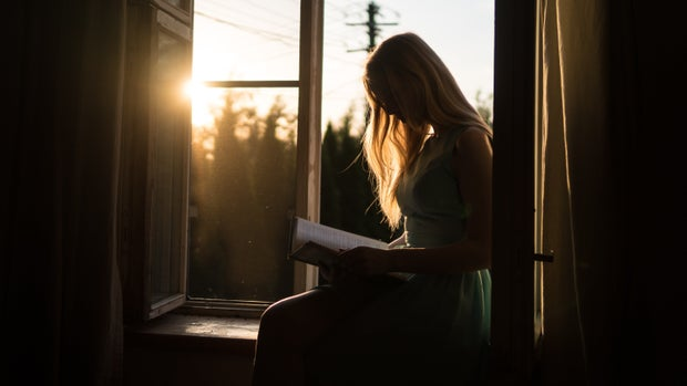 woman reading a book on a window seat