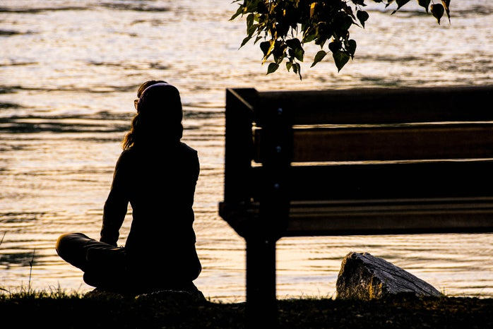 Woman sitting by the river at sunset