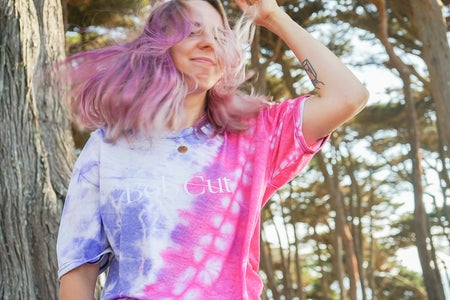 woman with pink hair in blue and pink tie dye shirt in forest
