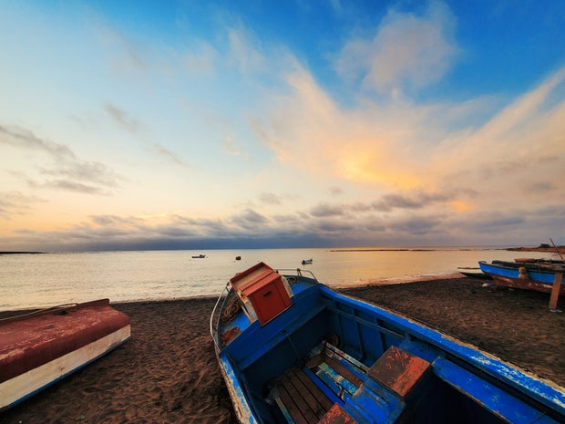 blue and red boat on beach during daytime photo in Cape Verde