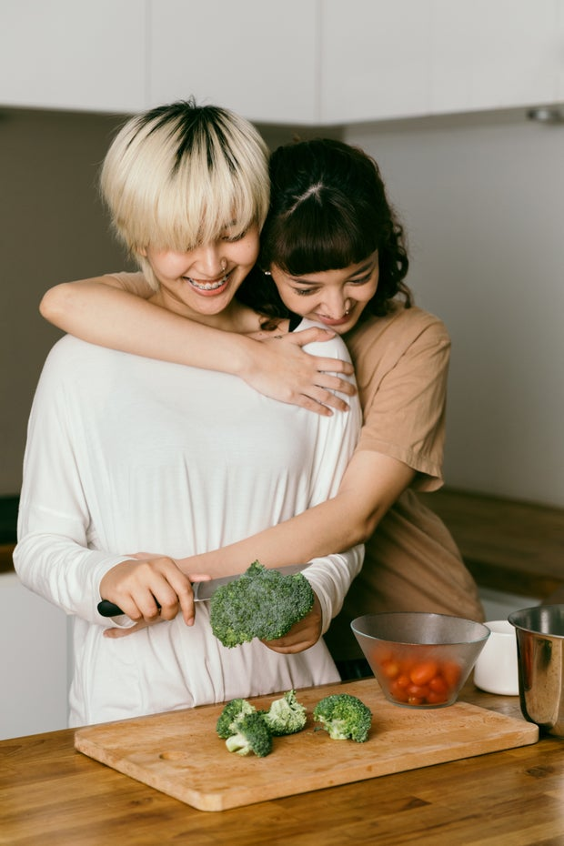 woman being hugged while cooking