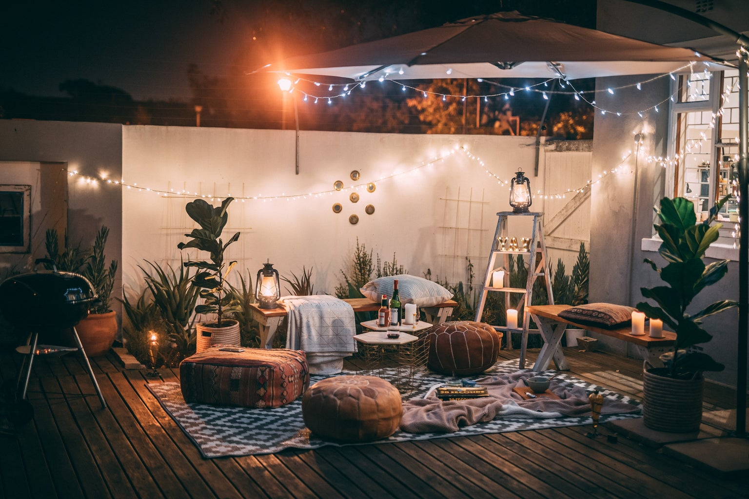 An outside setup with lots of cushions and some fairy lights. There are also plants everywhere and a small table that has drinks.