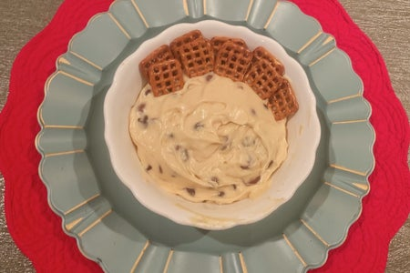 Cookie Dough Dip with Dipping Pretzels is Served in A White Bowl on top of a red and blue placemat display