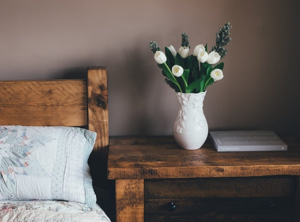 white flowers in vase on bedside table