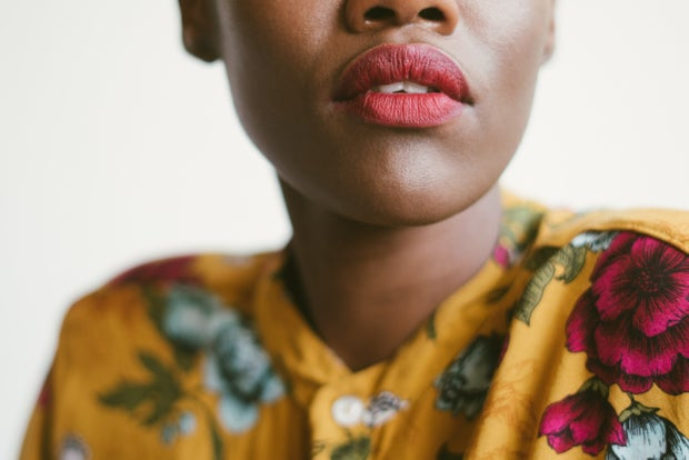 Bottom half of black african woman's lips with pink lipstick