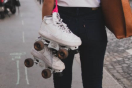 white roller skates hanging off a pink string; black jeans and brown bag.