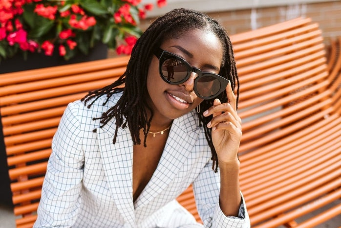 Woman in suit and sunglasses sitting on bench