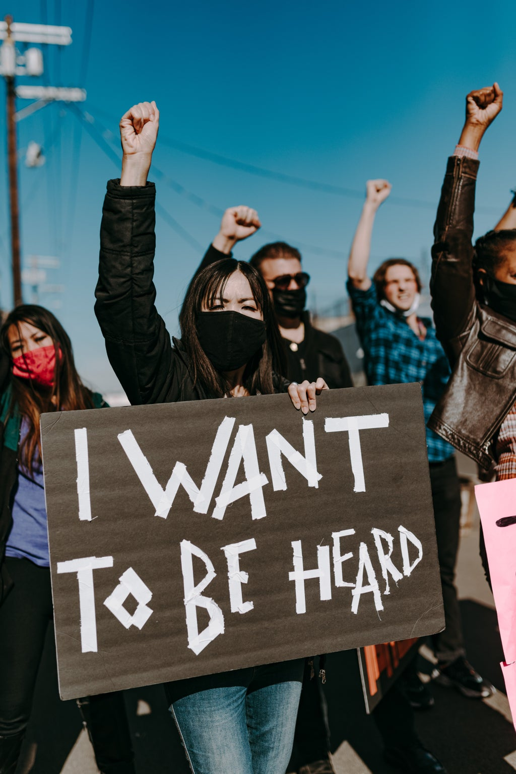 """Woman holding a sign that reads, \""""I want to be heard.\"""""""